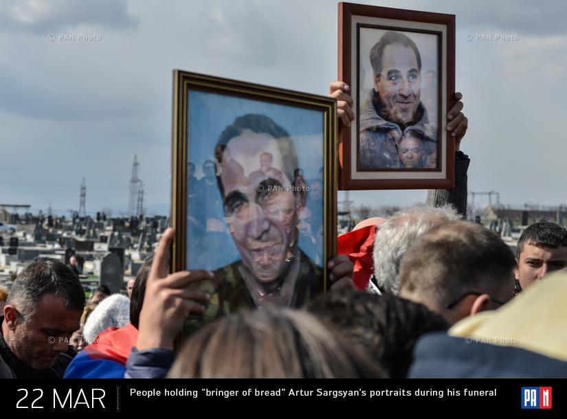 Граждане держат в руках портреты «приносящего хлеб» Артура Саргсяна во время его похорон