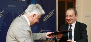RA Minister of Economy Vahram Avanesyan and AJA vice president Artak Udumyan sign a contract