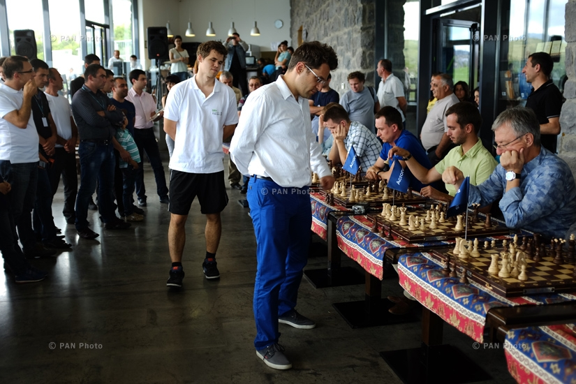 Magnus Carlsen and Levon Aronian play simul on 10 boards with monks and residents of Tatev
