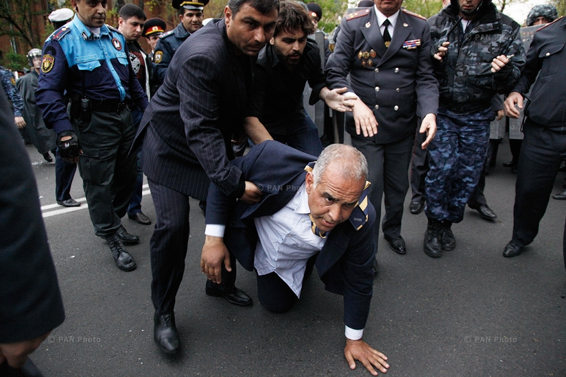 Armenian election runner-up Raffi Hovanisian is helped up after he fell during clashes between his supporters and police in Yerevan, Armenia