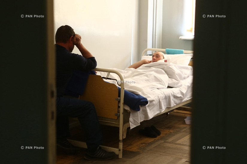 A man sits next to his son in Central Hospital of RA Defense  Ministry,  who has been injured in the course of military operations on the line of contact between Nagorno Karabakh and Azerbaijan