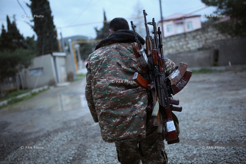 An Armenian fighter carries Kalashnikov machine guns to his comrade-in-arms at Martakert province of Nagorno-Karabakh Republic